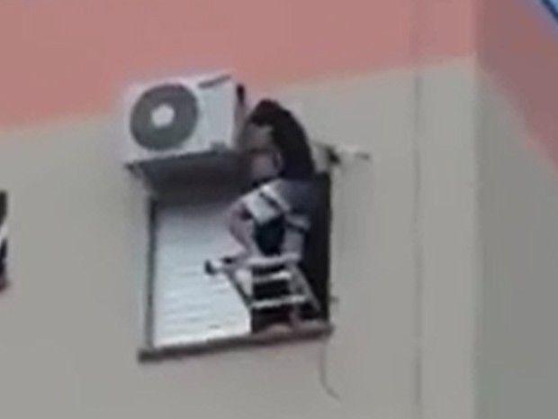 Homem faz a manutenção do ar em prédio de Araçatuba (Foto: Reprodução/ TV TEM)